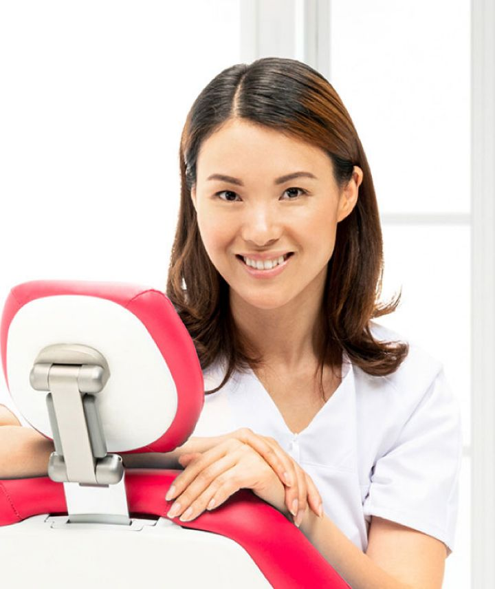 Portrætbillede af unge kvinde der smilende sidder i en tandlægeunit