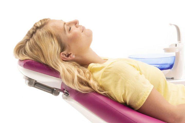 En glad patient læner sig tilfreds tilbage og hviler hovedet på nakkestøtten af patientstolen på en tandlægeunit