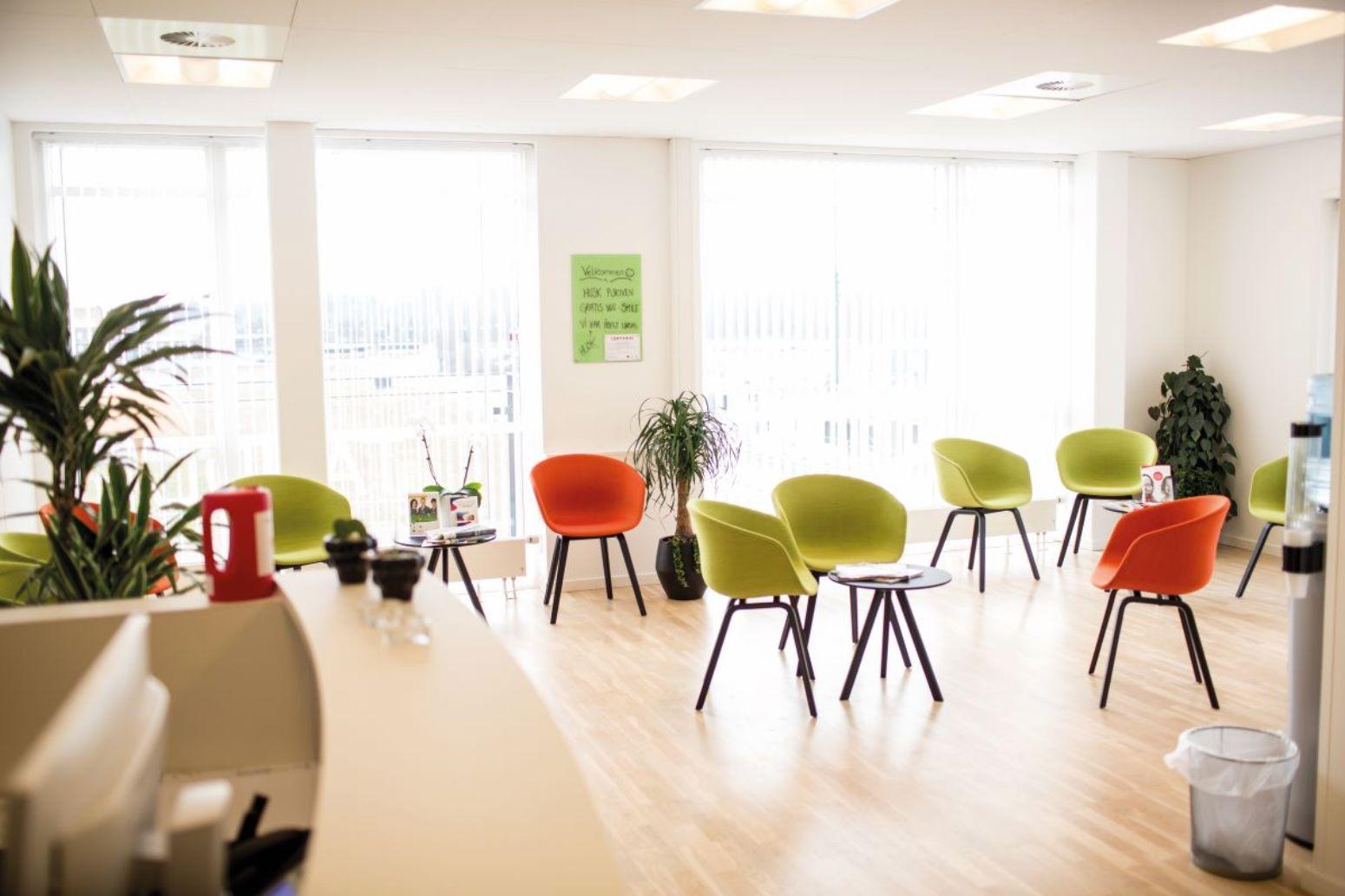 En tandlægereception som viser muligheder for indretning med farvede stole i lime og orange farver i et lyst lokale med flot lysindfald