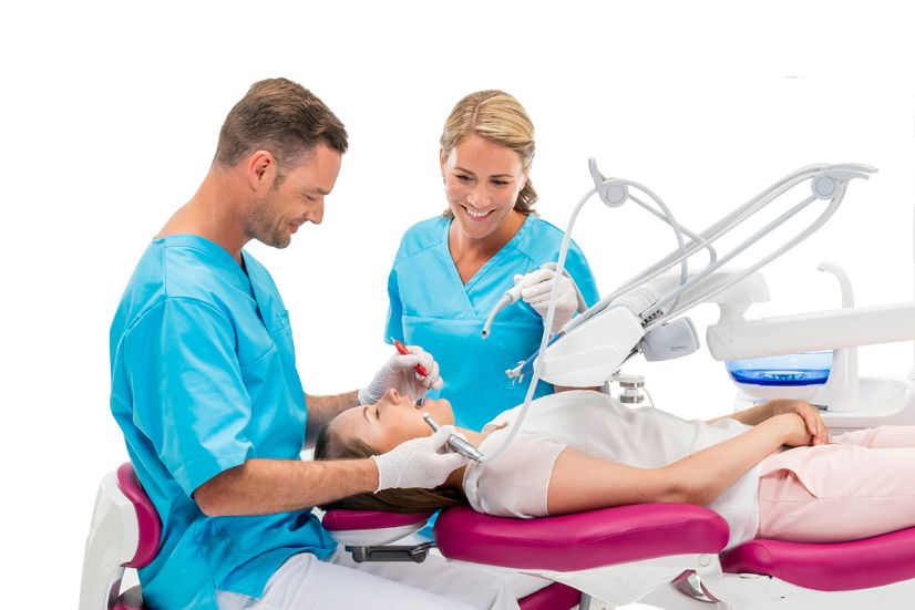 En tandlæge og en klinikassistent er i gang med en behandling hvor man kan se at der er god plads til begge to omkring tandlægeunitten